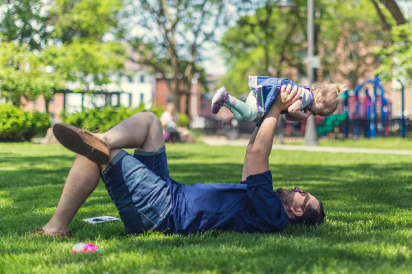An image of a father and son playing in a sunny park.